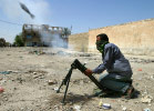 An Mehdi militiaman loyal to the radical Shiite cleric Muqtada al-Sadr, fires a mortar round at a U.S. army position in Sadr City.