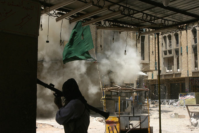 A Mehdi Militia fighter takes cover behind a brick column as U.S. shells hit a nearby building.