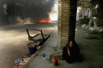 An elderly woman sits in the street 50 meters away from the shrine of Imam Ali in Najaf shortly after an intense battle between U.S. forces and Mehdi Militia.