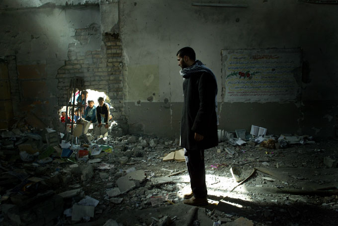 An Iraqi shiite man inspects the remains of the Tawheed mosque after a bomb blast. Witnesses said masked men planted explosives around the building early in the morning and then blew it up.