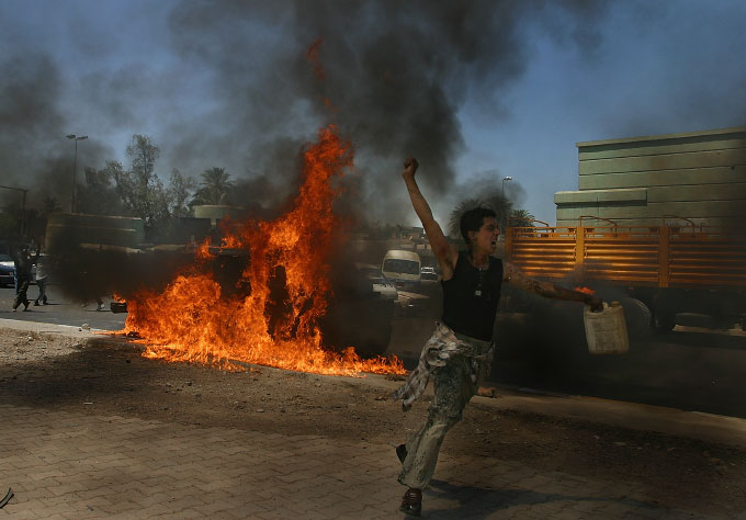 An Iraqi boy celebrates after setting fire to a damaged U.S. vehicle that was attacked earlier by insurgents.