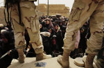 Women struggle to form a line at a gas distribution center. The U.S. army, in cooperation with the former Iraqi government's distribution ministry, set up the center to provide essential fuel for cooking and water purification.