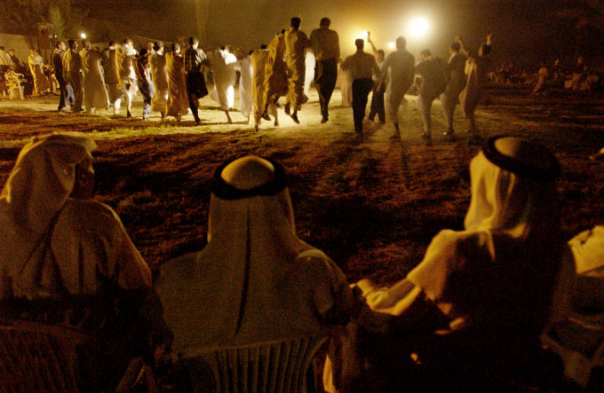 Younger men leap during a wedding dance while older men watch from the wings at a nighttime wedding celebration in Deshah village in the Ramadi district. Ramadi is located inside the {quote}Sunni Triangle,{quote} the heartland of proud Sunni tradition.