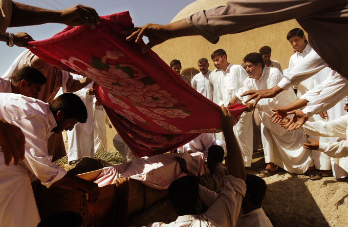 Mourners prepare to lower the body of Sheikha Beijiya into her grave in a cemetary near Fallujah. The elderly woman was killed -- along with her daughter, son-in-law, and one-year-old grandson -- by American soldiers who say they opened fire on the family's car when it failed to stop at a temporary checkpoint on the road from Fallujah to Baghdad.