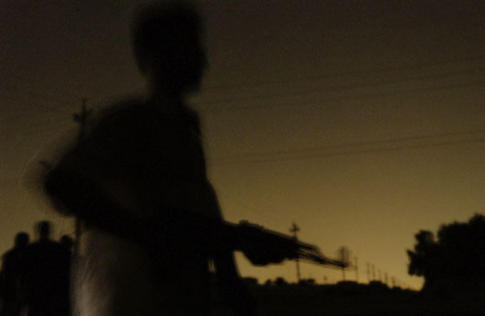 A Mehdi Militia night patrol guards an intersection in Sadr City in anticipation of an American incursion. The Mehdi Militia is the armed wing of a Shiite anti-occupation movement led by the young cleric, Muqtada al-Sadr.
