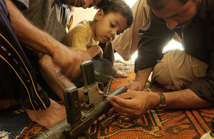 A young boy watches his relatives repair a rocket propelled grenade launcher in the home of a Shiite fighter for the Mahdi Militia in Sadr City.