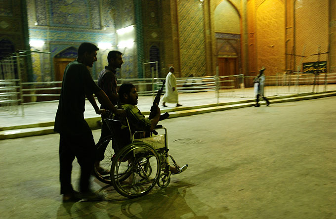A wheelchair-bound member of the Mehdi Militia takes a nighttime tour of the outer walls of the Imam Ali shrine. The shrine was at the center of a three-week American seige of the old city of Najaf where Mehdi Militia fighters loyal to Muqtada al-Sadr staged a rebellion against the Iraqi government and American military occupation.