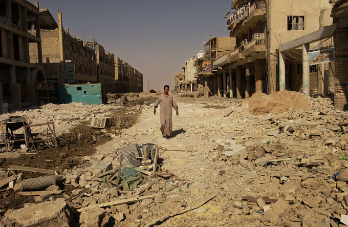 A lone man walks through a thoroughly destroyed business and residential street west of the Imam Ali shrine in Najaf. The street was a front line fighting position for American army and Mehdi Militia fighters during a nearly three-week battle that left much of the old cit of Najaf and surrounding neighborhoods in ruins.