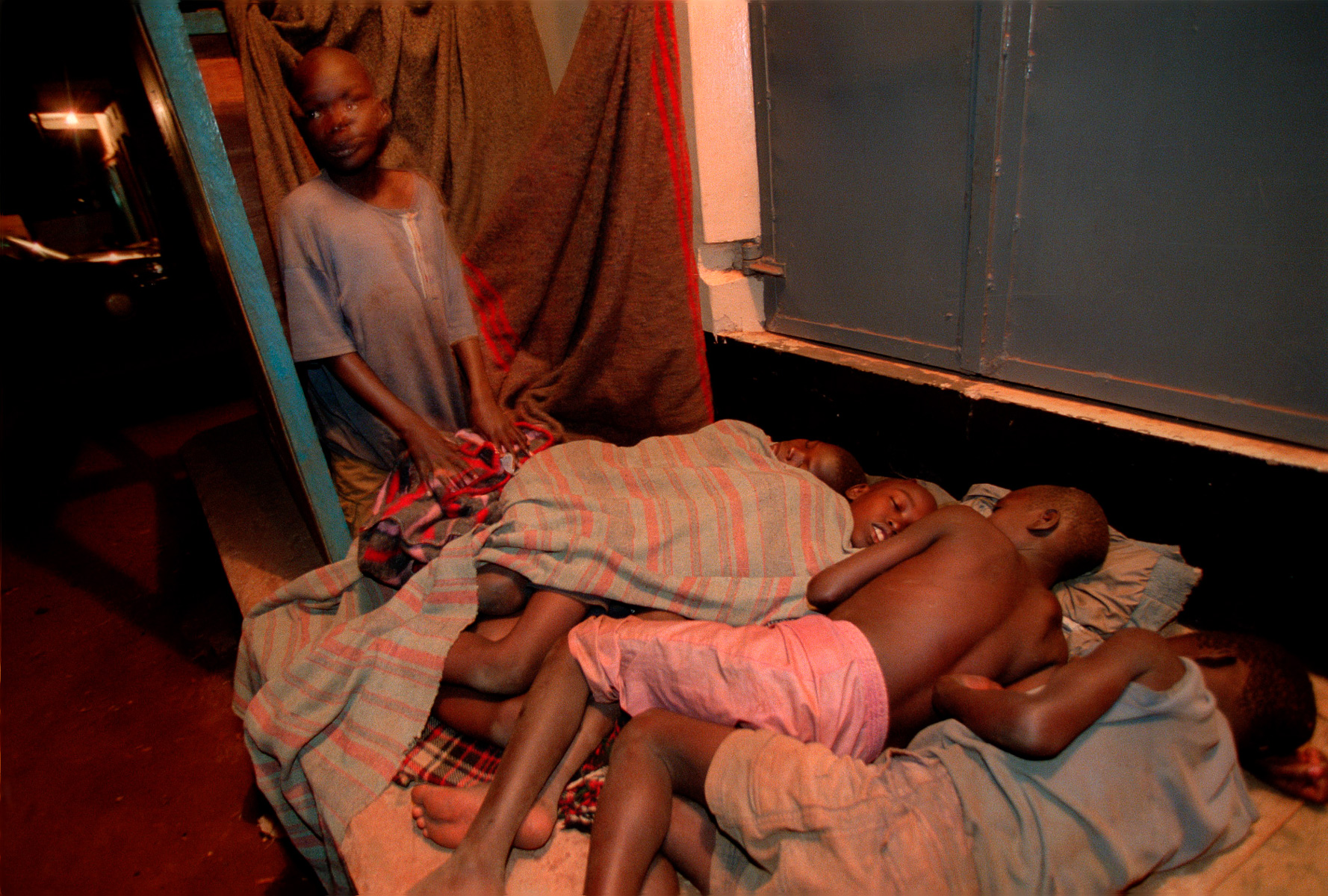 Children sleep at the bus park in Gulu. It is estimated that 40,000 children leave their villages every night to sleep at hospitals, churches, towns or wherever they feel more safe from abduction by the Lord's Resistance Army. They are called night commuters. Uganda.