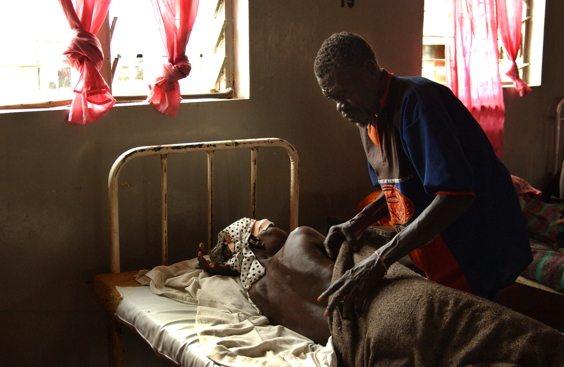 Duculina Abalo is cared for by her husband Lino Ochia at Kitgum hospital. She was on her way to collect mangos with another man when Lord's Resistance Army rebels attacked them leaving her with serious head injuries. The man has not been seen since the attack. Uganda.