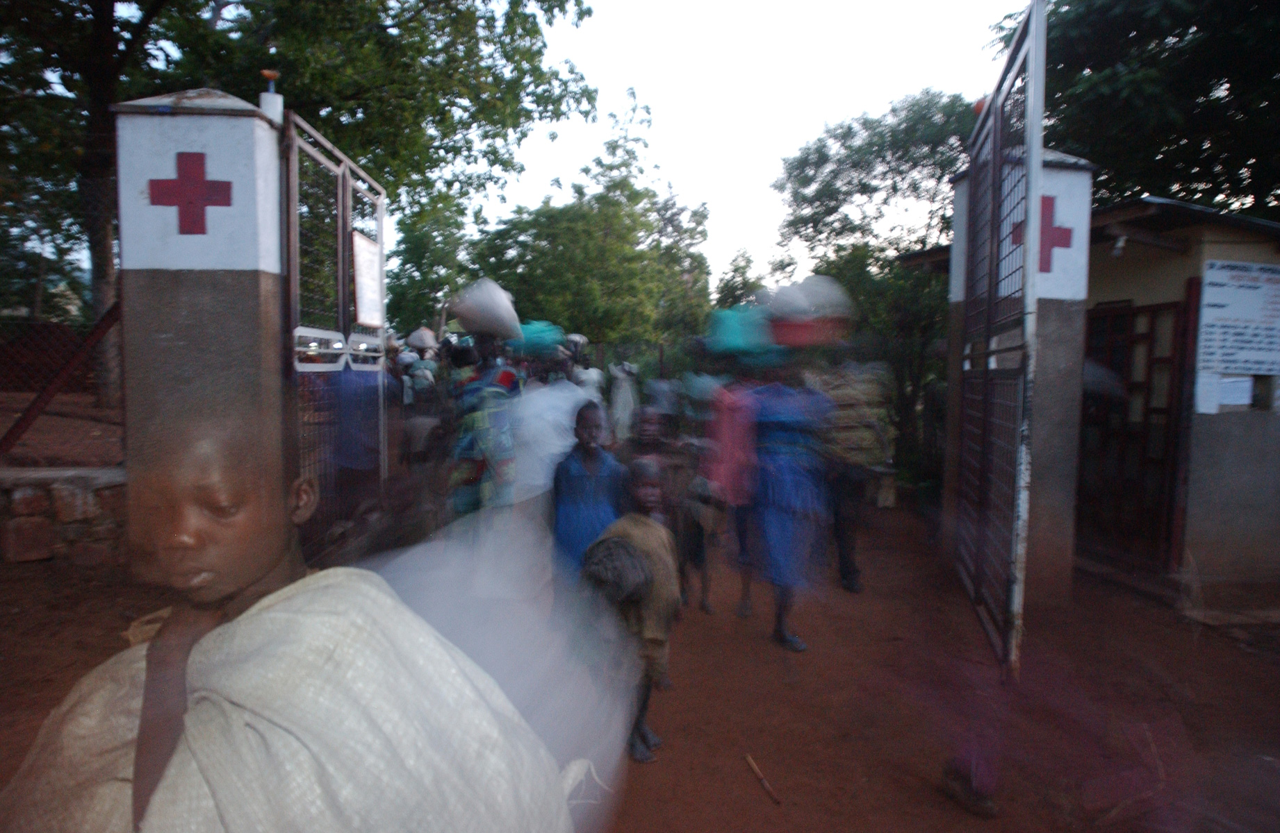 Women and children pour into Ambrosoli Memorial Hospital Kalongo hoping to avoid abduction by the Lord's Resistance Army. The internally displaced people's camp or protected camps as referred to by the Ugandan Government lies just on the other side of the chain link fence but security is so bad they come inside the hospital grounds by nightfall seeking protection. Uganda.