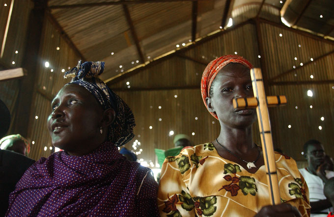 In Kapoeta, worshipers attend Sunday morning prayer in a church scarred with bullet holes.