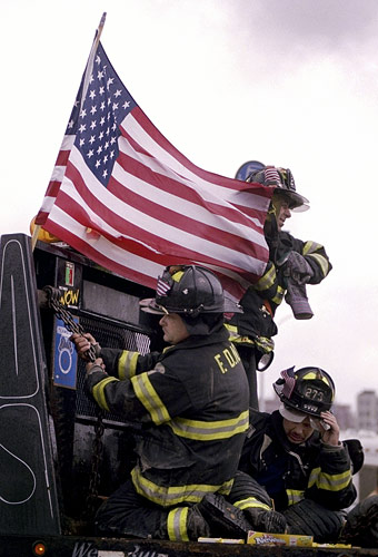Firefighters ride on the back of a flatbed truck towards Ground Zero.