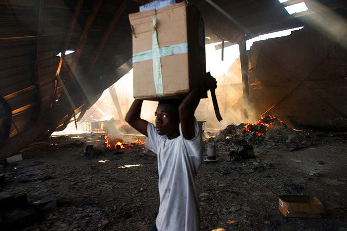A boy loots the main supply terminal at the port in downtown Port Au Prince.