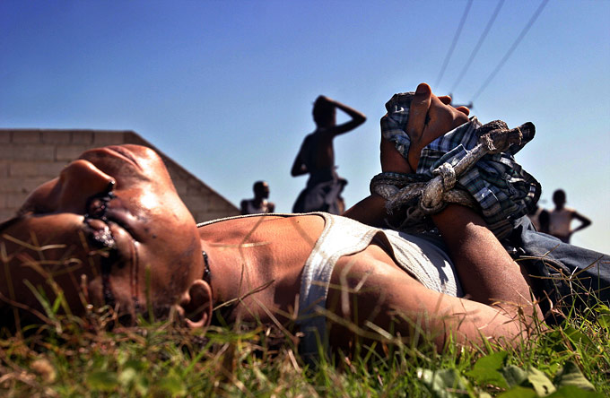 The body of a young man who was executed lies on the roadside outside of Port Au Prince.