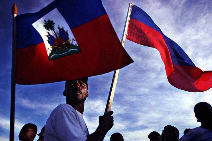 Residents of Gonaives hold their national flag during a patriotic street rally.