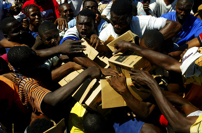 Men struggle to collect food being distributed in front of the presidential palace in Port Au Prince.