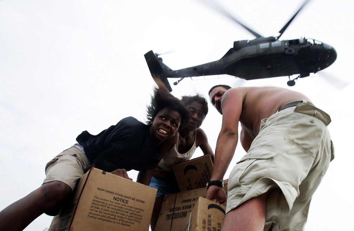 Stranded New Orleans residents collect food dropped by an U.S. Army helicopter outside the Convention Center New Orleans, LA on Sept. 5, 2005, almost a week after Hurricane Katrina made landfall in the area.  Thousands were left stranded at the facility after being evacuated to the facility prior to the storm.