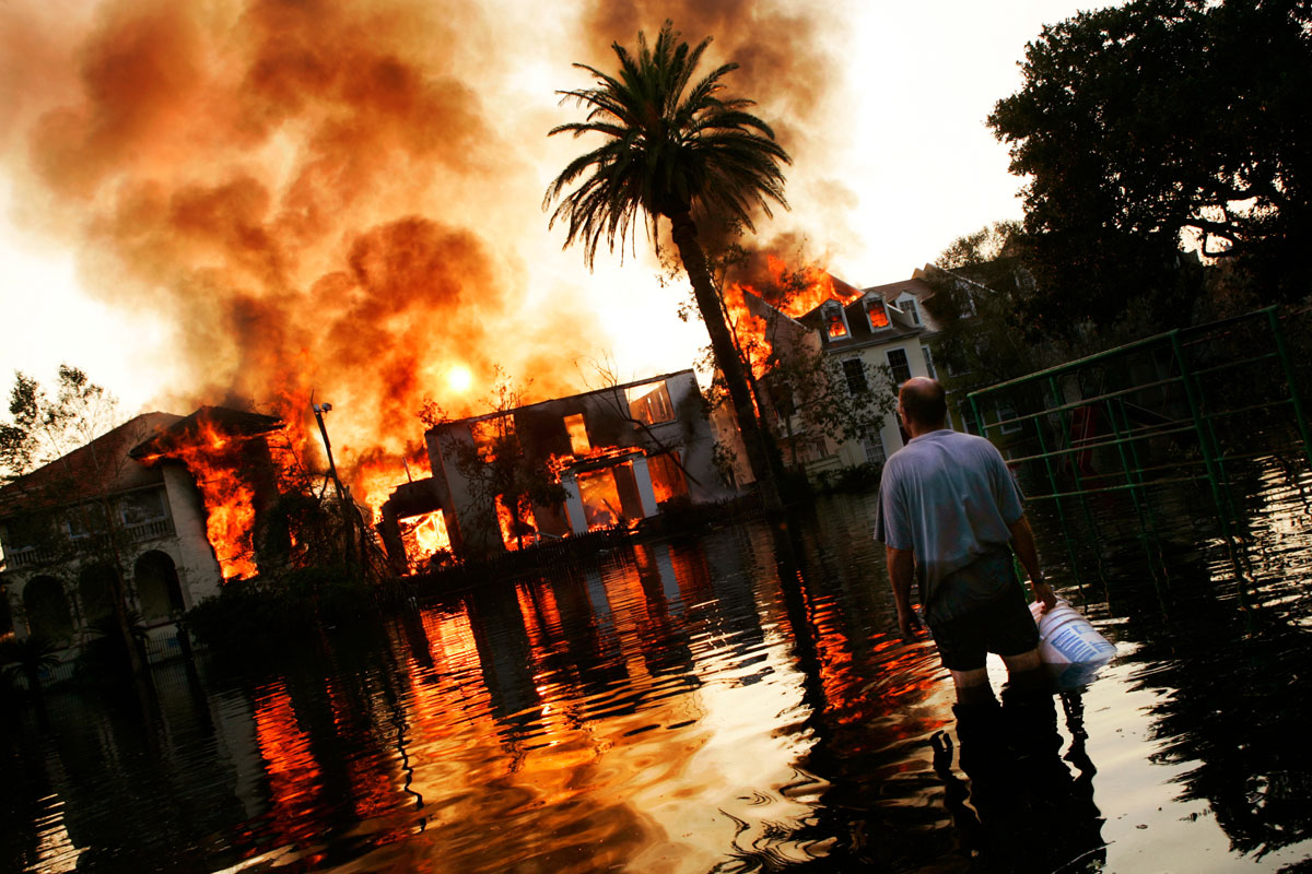 A man watches with bucket in hand while a row of houses burns out of control in the Garden District neighborhood of New Orleans, LA on Sept. 4, 2005, almost a week after Hurricane Katrina made landfall in the area.    Because of severe flooding emergency personnel were unable to respond to the blaze in a timely manner.
