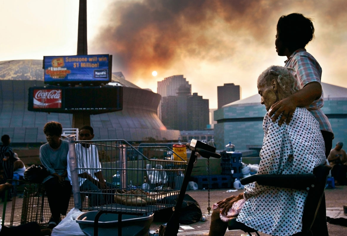 Ann-Veronica Recasner, right, and her mother Mildred Foley, 90, sit with other stranded New Orleans residents on an overpass in downtown New Orleans on Sept. 3, 2005, where they spent four days without shelter following the landfall of Hurricane Katrina.  They were rescued by National Guardsman later that morning.