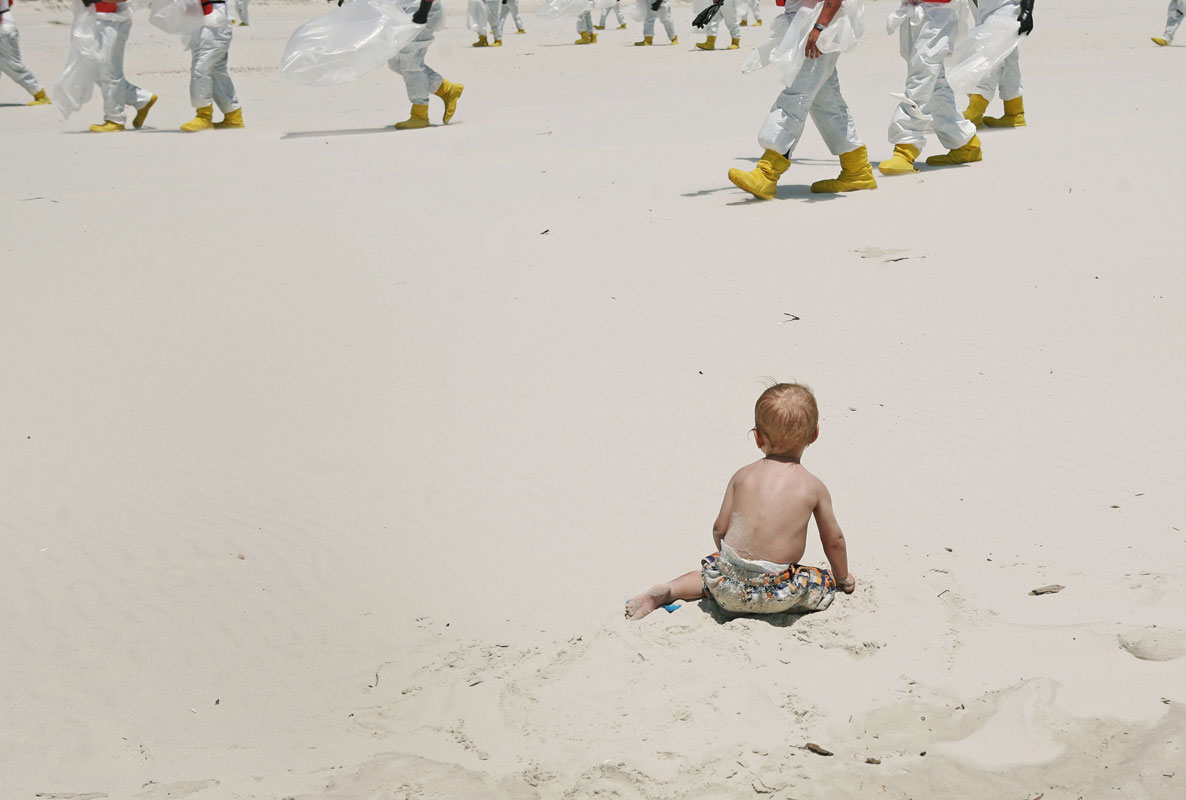 A cleanup crew wearing protective suits walks past a small child playing in the sand on a beach on Dauphin Island, Alabama, on Wednesday, May 12, 2010, as they comb the beach for traces of oil from the Deepwater Horizon oil spill.   The spill released millions of barrels into the Gulf of Mexico over a three month period.  Its long-term impact on the region is still unclear.