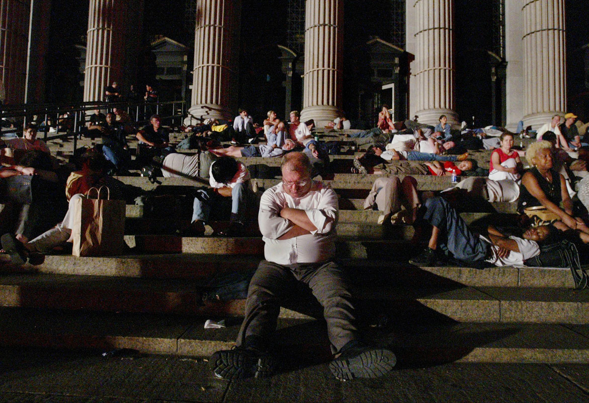 Commuters sleep on the steps of the James Farley Post Office on Eighth Avenue in New York City during the early hours of Friday, August 15, 2003, after being stranded because of a massive electrical blackout.  The blackout affected everything from trains to mobile phones and occurred across much of northeastern United States and Canada.