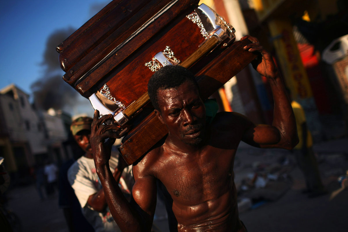 Men carry a coffin through the streets of Port-au-Prince, Haiti on Monday, January 18, 2010 a week after the country was struck by a magnitude 7.0 earthquake, killing thousands.