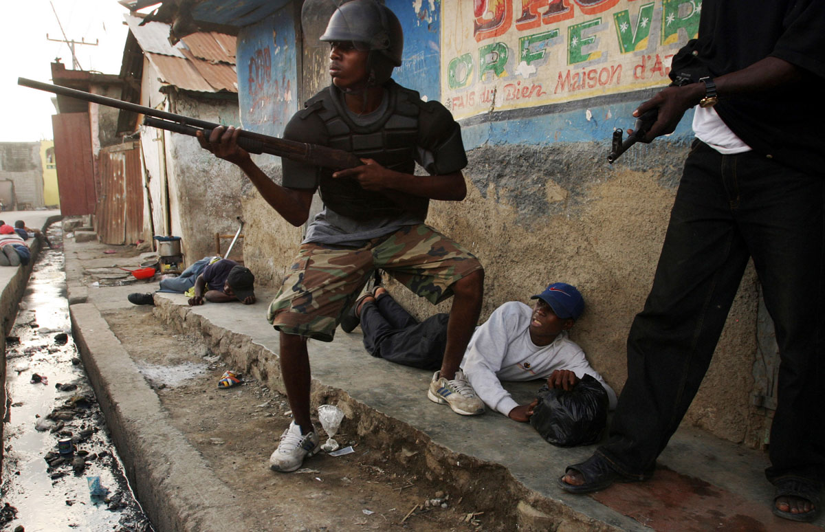 Residents of Cap Haitien, Haiti lay on the ground as Rebel forces search for a suspected gunmen loyal to President Jean-Bertrand Aristide who fired on them on Feb. 23, 2004.  The Rebels took control of the city, Haiti's second largest, the day before but continue to encounter resistance there from forces loyal to President Aristide.