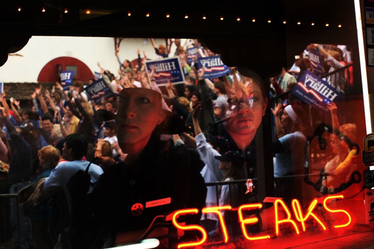 Waitstaff watch from the window of a restaurant as supporters of Presidential hopeful Hillary Clinton attend a large outdoor rally at the Stockyards in Fort Worth, TX on March 1, 2008, on the Saturday before the State's primary election.