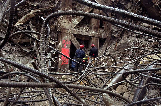 Members of FDNY's Rescue Three Unit look into a space in the pit of Ground Zero where the remains of a fellow firefighter are known to rest.