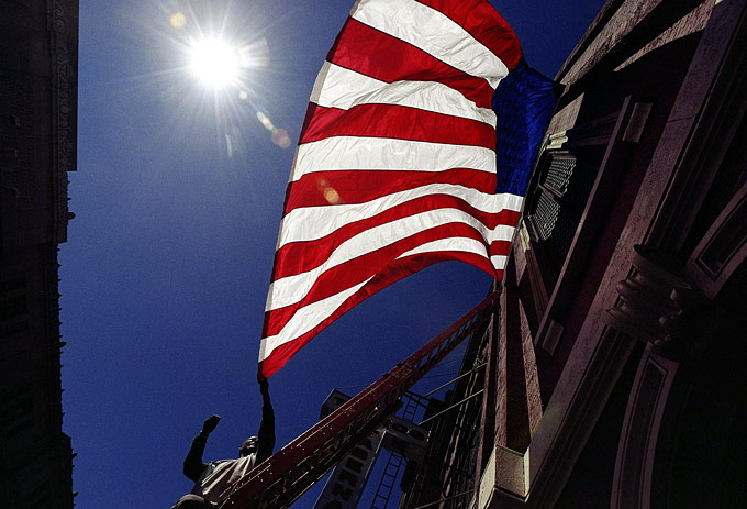 A man hangs an American flag outside a church in Manhattan the day after 9/11.