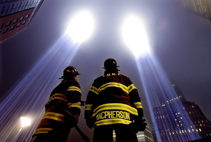 Firefighters John Leimeister, left, and Sean MacPherson of Engine 292 pause to look up at the Towers of Light Tribute before continuing their search for human remains at Ground Zero.