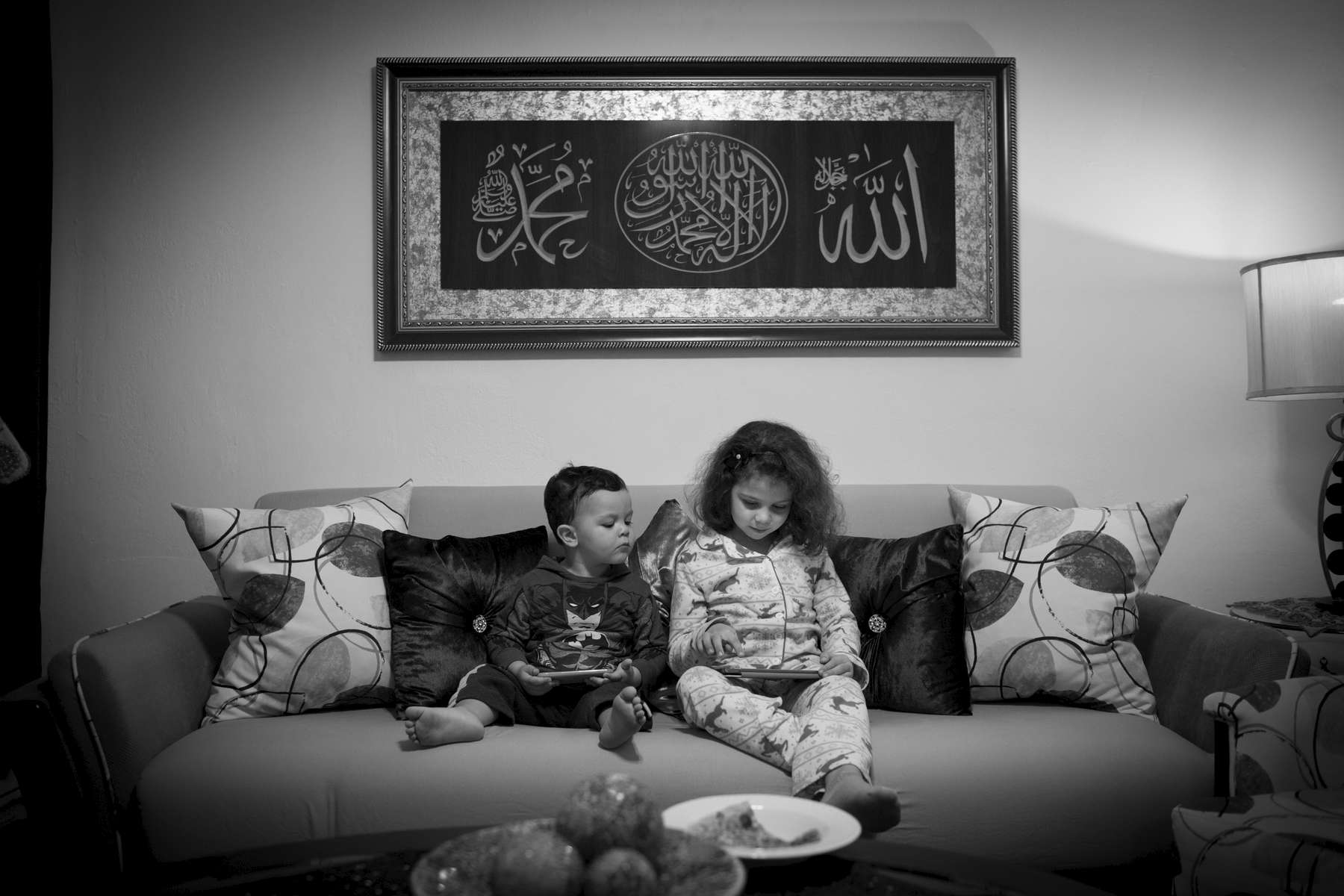 Souad and two-year-old Hassan play on mobile devices as they sit together on the living room sofa. Michael Appleton/Mayoral Photography Office
