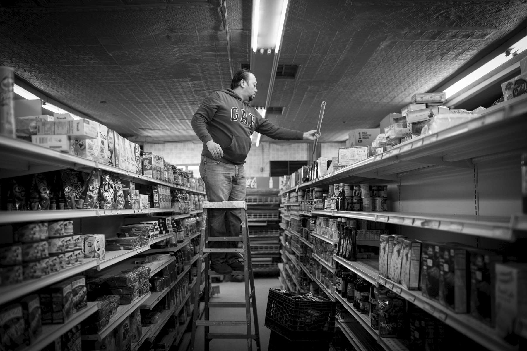 Abdullah Ferdous, who works as an electrician, changes a lighting fixture at a food market in Brooklyn. Michael Appleton/Mayoral Photography Office