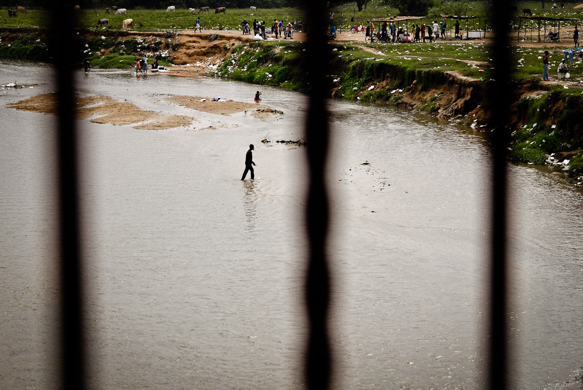 Haitian man crossing the Massacre river at the Haitian-Dominican border in Dajabon, Dominican Republic.
