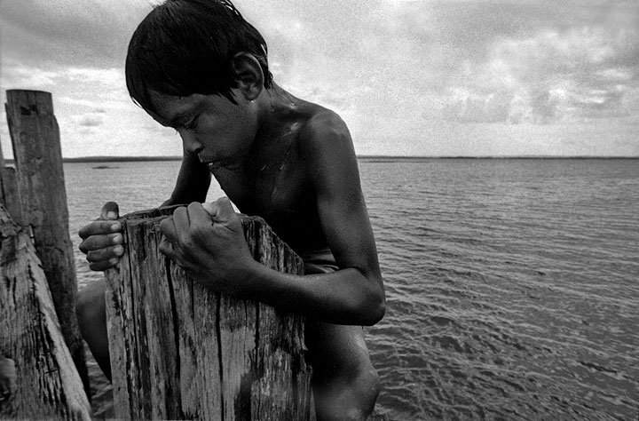 A boy climbing out of the Tapajos River after diving.Amazon, Brazil