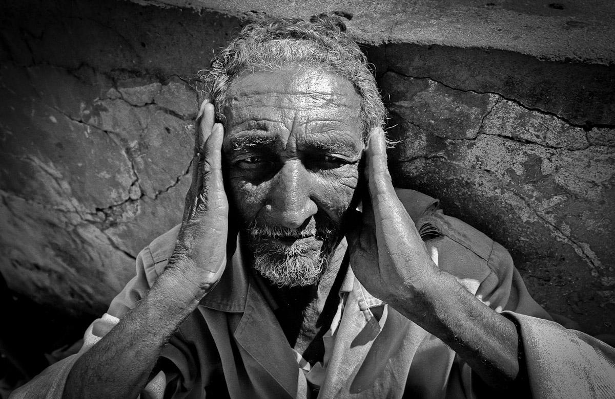 A blind pilgrim praying outside of a church