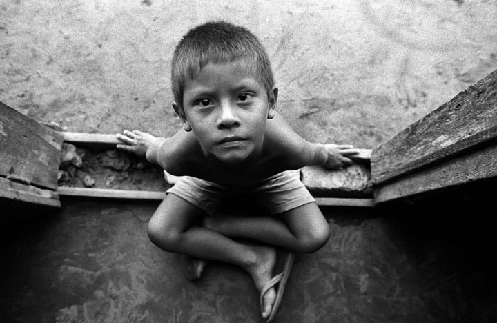 After photographing a family inside their home in the town of Boim, a curious boy who had been watching was sitting at the doorway. Amazon, Brazil
