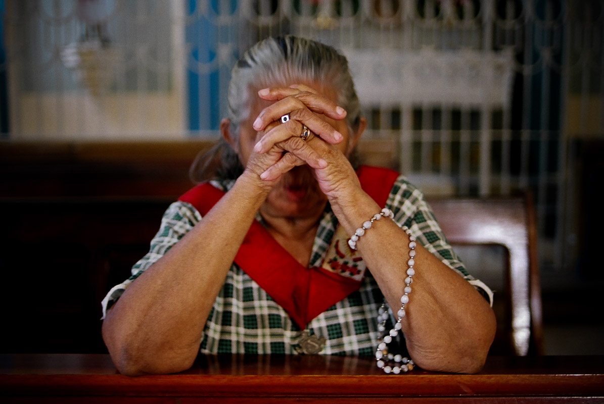 Woman praying after a mass service in Juazeiro do Norte.