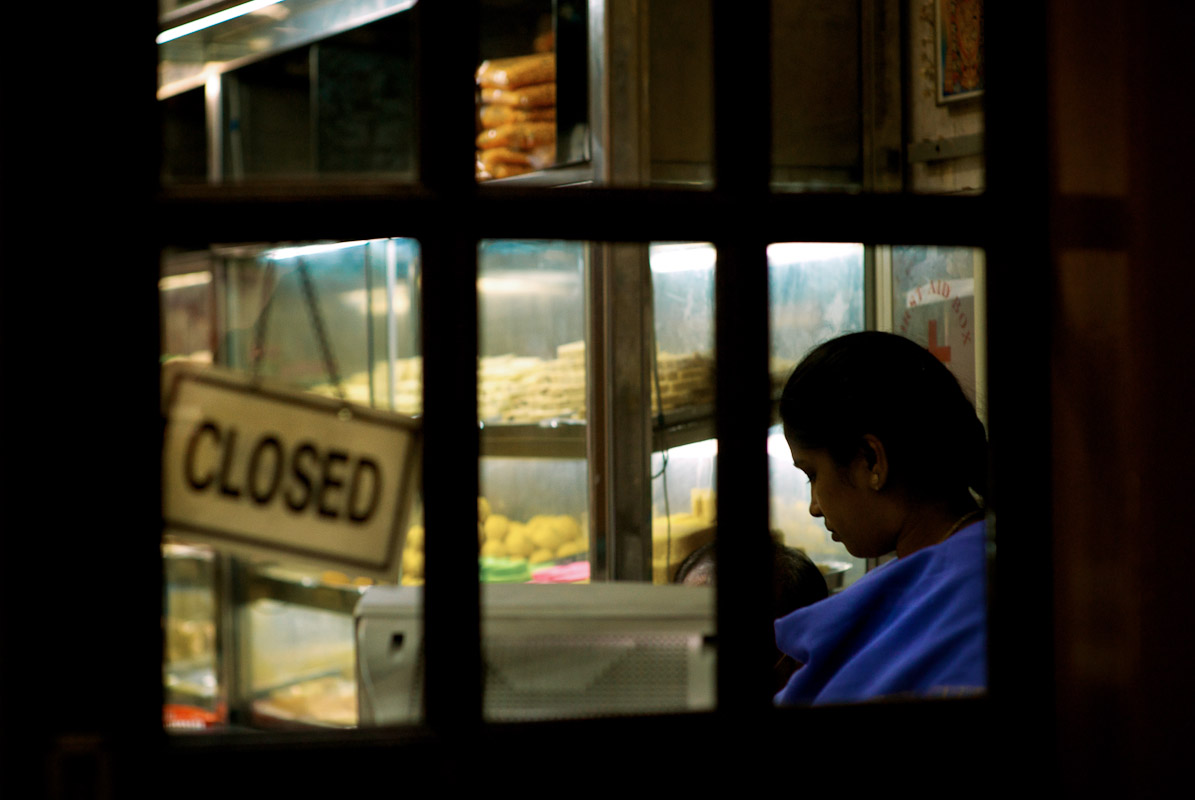 A woman closing her bakery shop in the Little India neighborhood of Singapore.