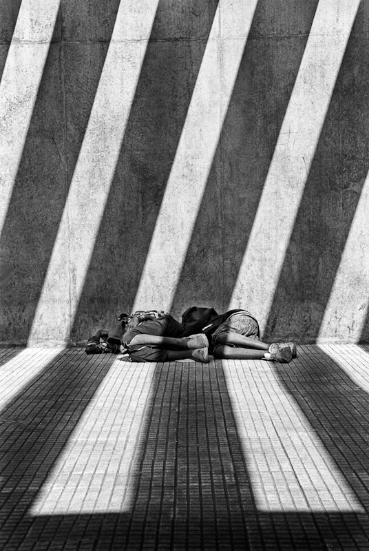 Two boys sleeping outside a metro station in Sao Paulo. When I  was exiting the metro and first saw this scene of the street children sleeping, my first impression was that of a jail cell with the way the strong light from above created dramatic shadows and contrast.