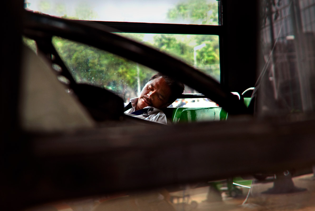 Bus driver taking a nap while on a break in Mexico City, Mexico.
