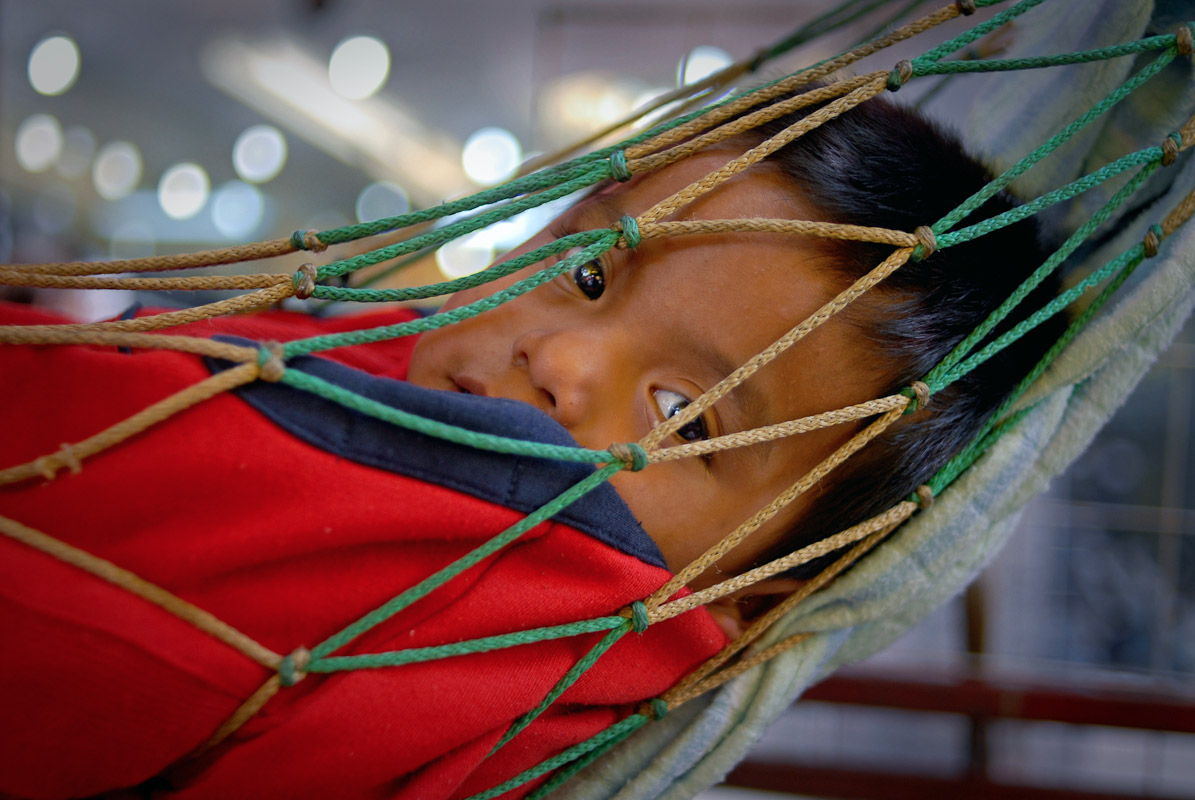 Boy resting in a hammock at an open market in Mexico City, Mexico.