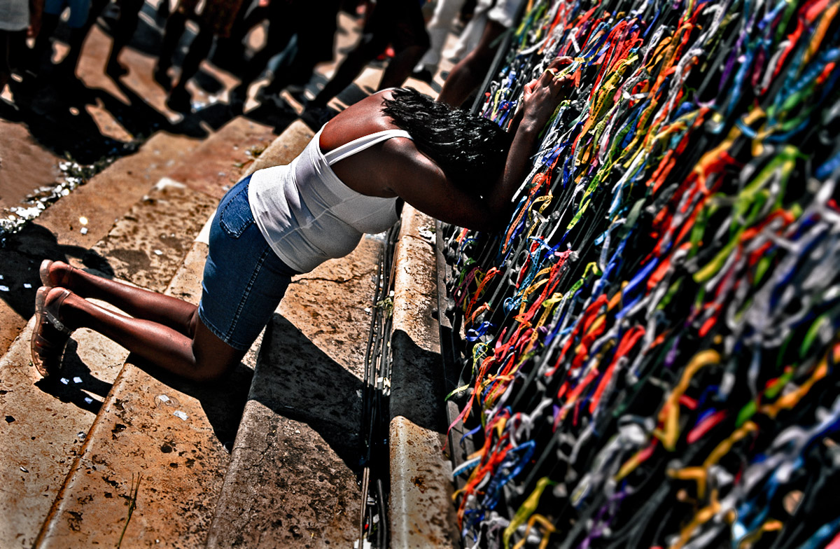 A woman praying in front of the Church of Bonfim. People tie colored ribbons around the fence of the church and make wishes.