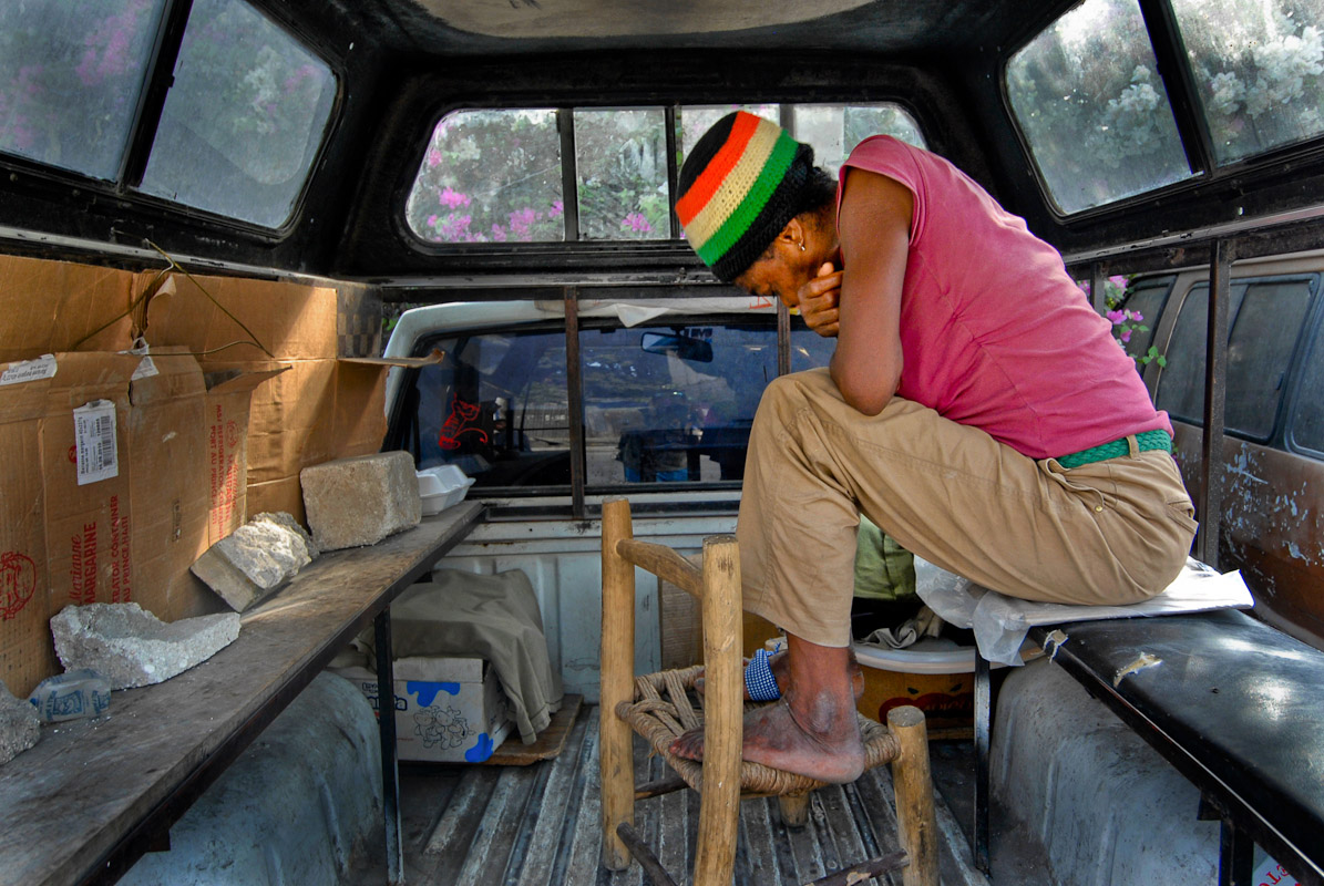 A woman in thought inside the back of a pick-up truck.