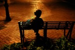 A woman sitting on a park bench after sunset.
