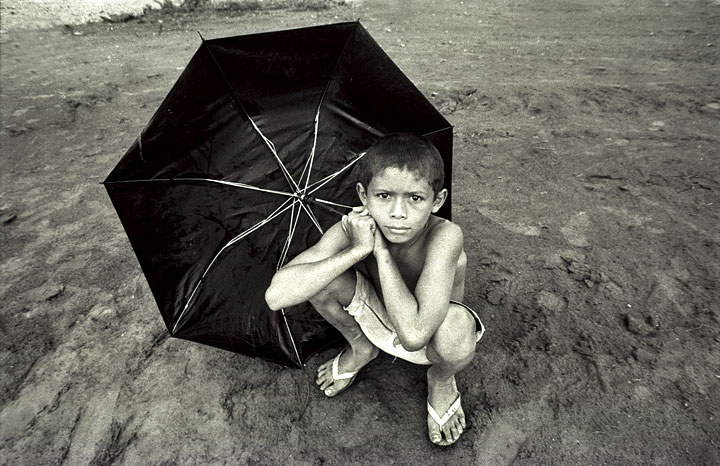 A boy sitting by the bank of the Tapajos River in the Amazon.Boim, Brazil