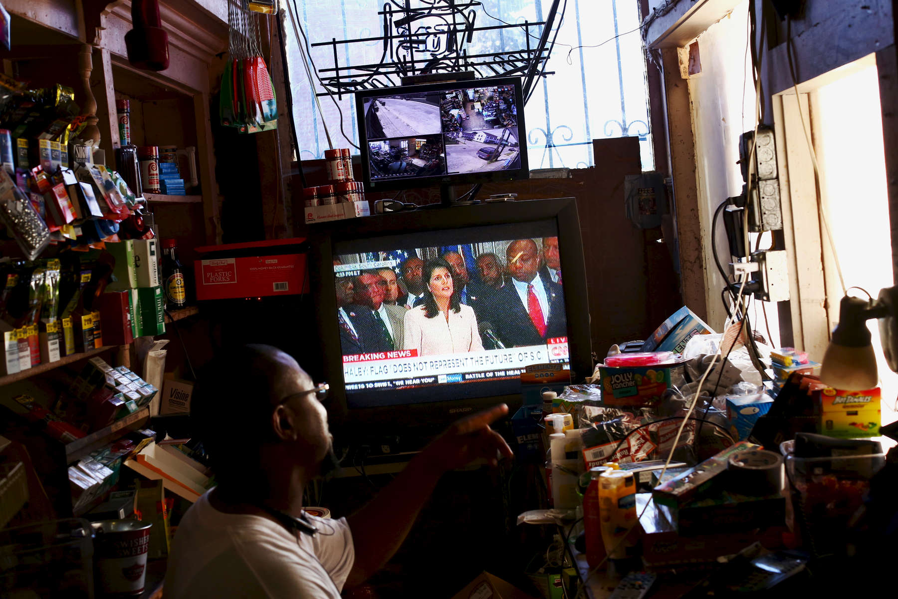 NAT *** Charleston, SC -- 06/22/2015 - A store owner watches Governor Nikki Haley speak about the Confederate flag on television on Monday in Charleston, SC.(Travis Dove for The New York Times)