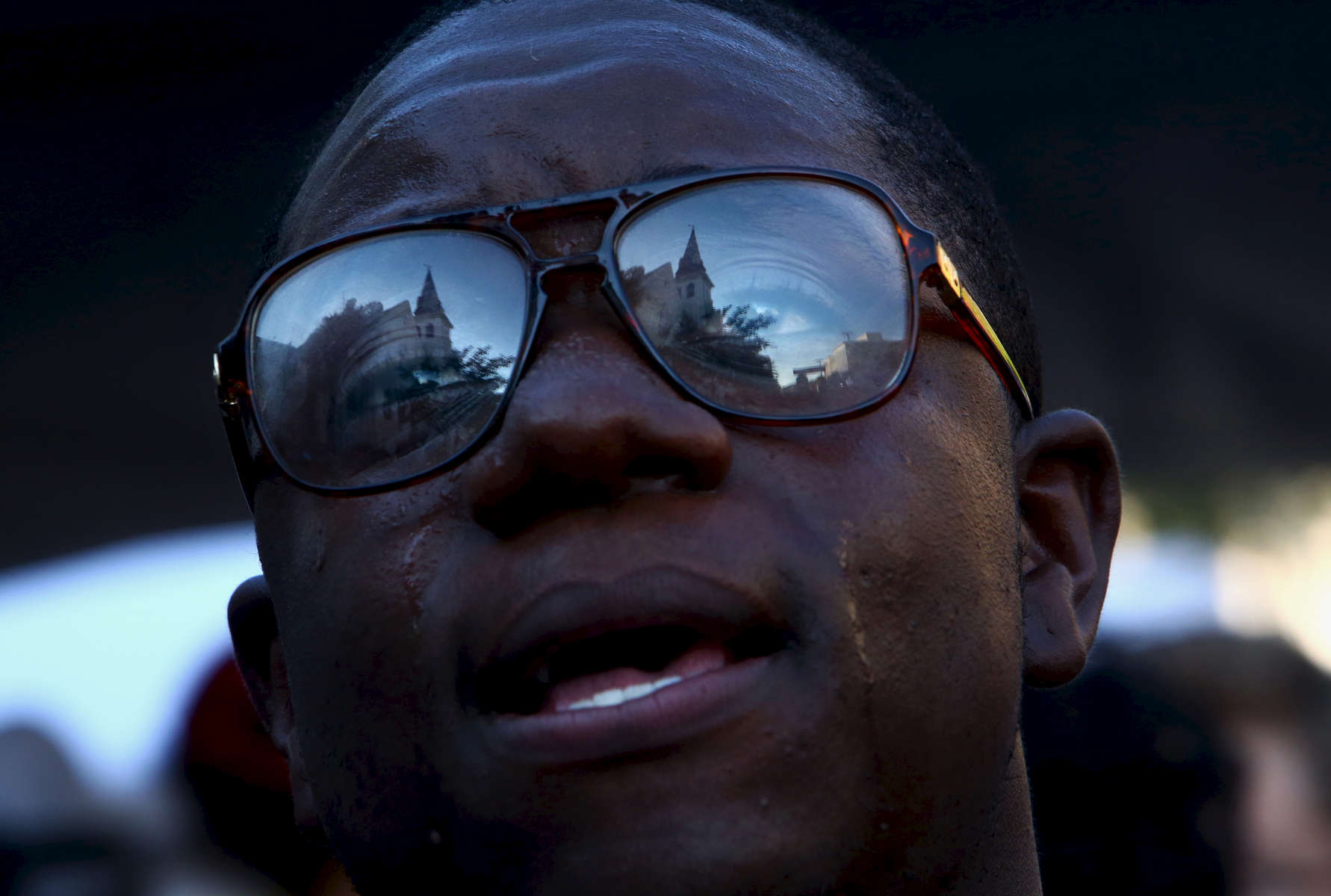 NAT *** Charleston, SC -- 06/20/2015 - Emanuel AME Church is reflected in the glasses of Michael Weeks of North Charleston as he sings outside on Saturday evening. (Travis Dove for The New York Times)