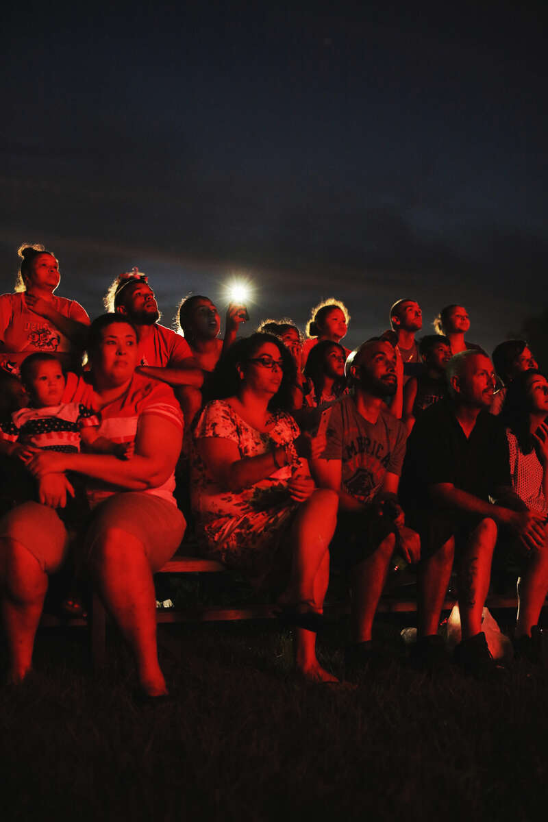 Lumbee homecoming attendees watch fireworks on July 7, 2018. The popular homecoming draws tens of thousands home to the small town of Pembroke, NC. The Lumbee tribe of eastern North Carolina is comprised of a people who's native identity—however culturally rich—has been fought over for more than a century by a federal government that doesn't see them fitting neatly into any racial category.